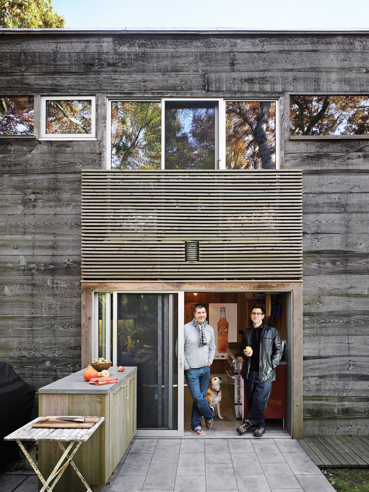 The patio is also equipped with a generous workspace. Bates's original fenestration, which failed to meet current building code, has been brought up to safety standards by employing the same slatting motif used elsewhere in the house. Tagged: Exterior, House, Wood Siding Material, and Flat RoofLine.  Photo 17 of 17 in Long Island Summer Home Gets a Modern Addition