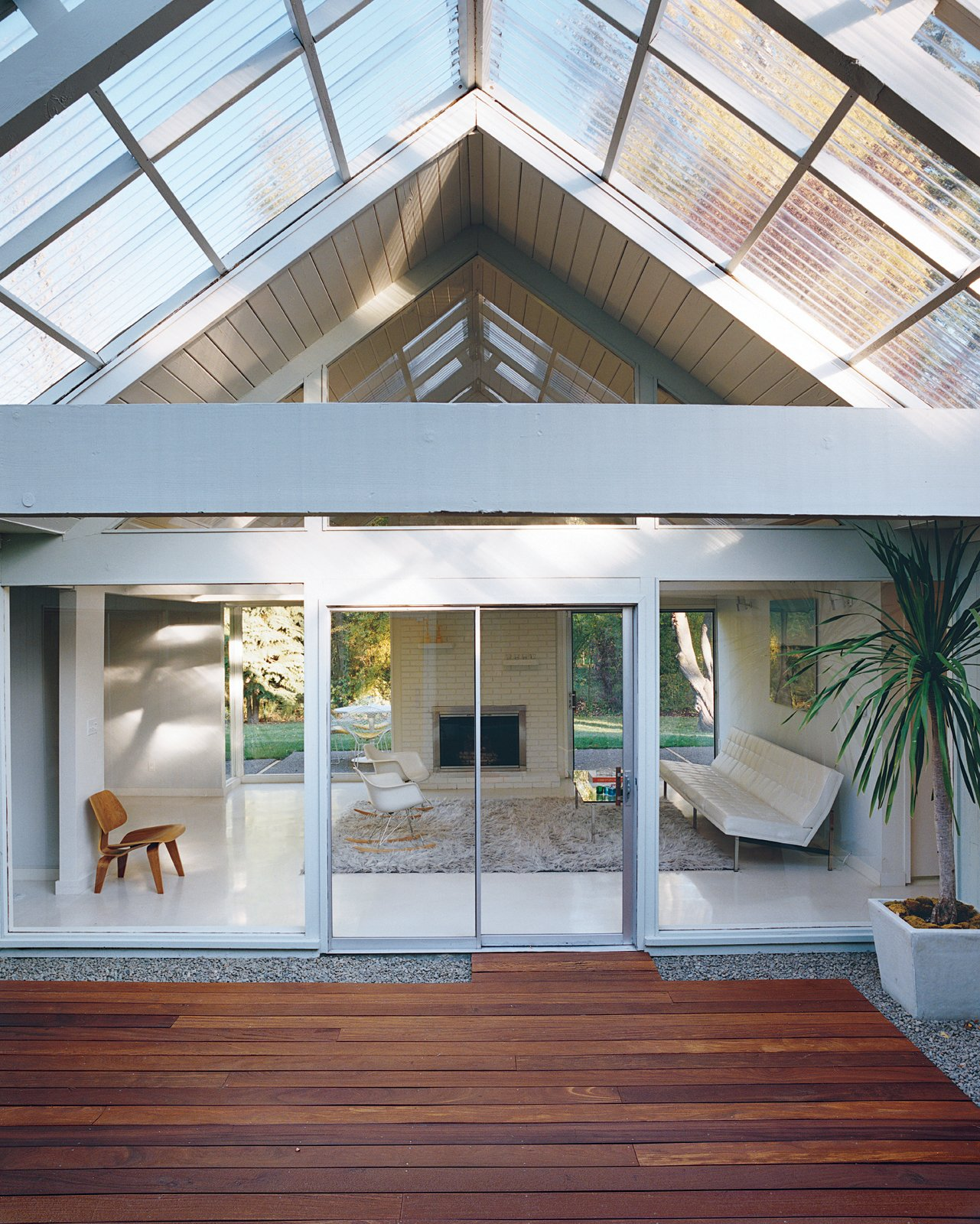 The literal and figurative centerpiece of the house is the atrium, through which light filters into the rest of the house year-round. Tagged: Outdoor, Large Patio, Porch, Deck, and Wood Patio, Porch, Deck.  Midcentury Homes by Dwell from A Mid-Century Modern Home in Southwest Portland