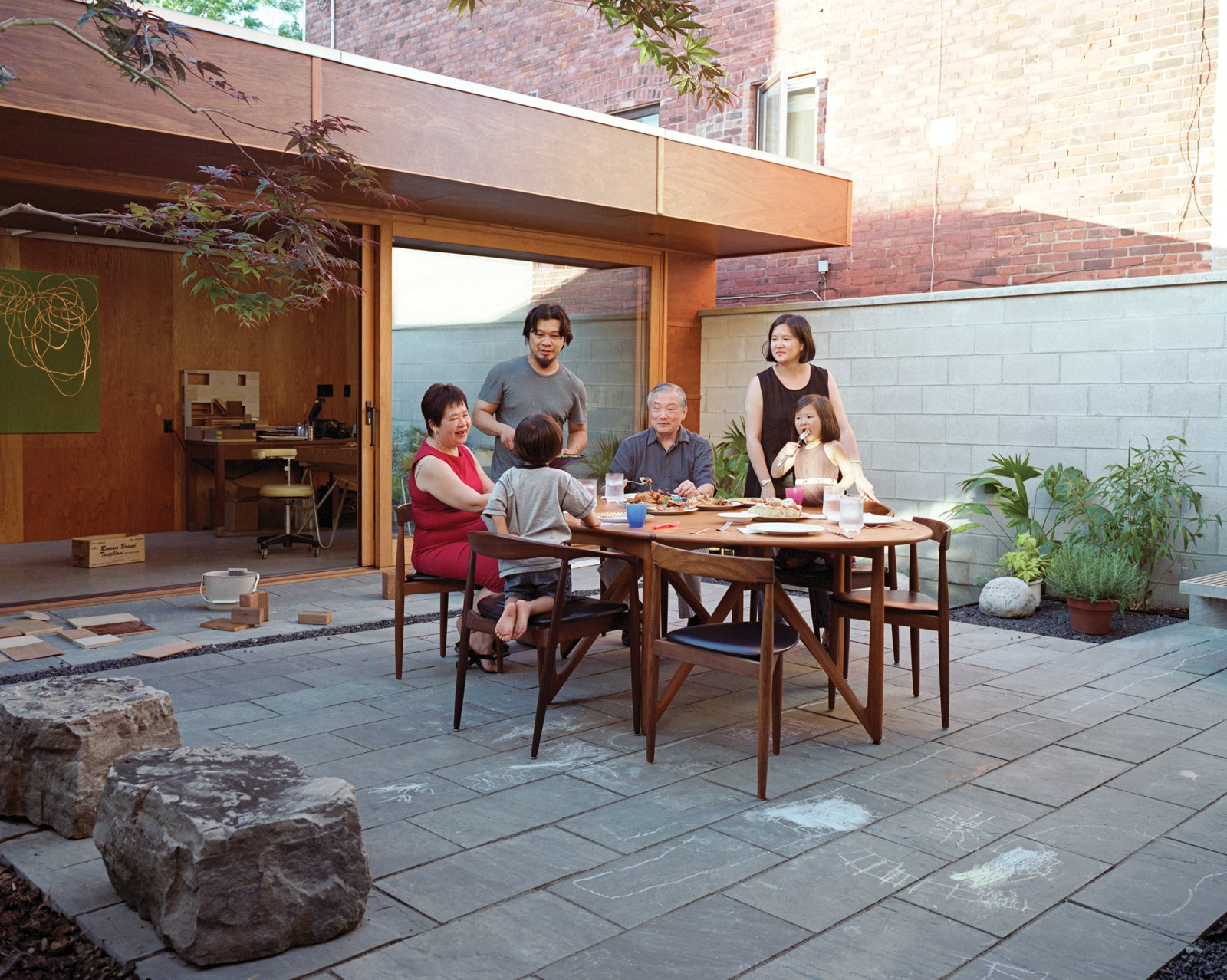 "The main courtyard is a ""communal"" space, Tan says, and the couple keeps a second teak dining set at the ready for occasions when family or friends come for a meal.  Photo 15 of 17 in Inside Job"