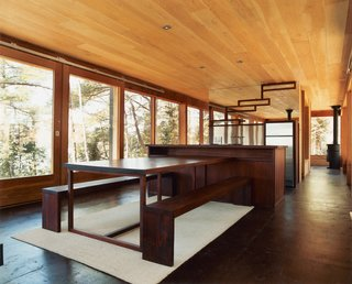 Eco-Friendly Rustic Cabin Retreat in Canada - Photo 1 of 4 - Barerock's minimal interior is augmented by a built-in dining area made from African padauk, a decay-resistant hardwood. The mirrored kitchen wall echoes the exterior's distinguishing feature.
