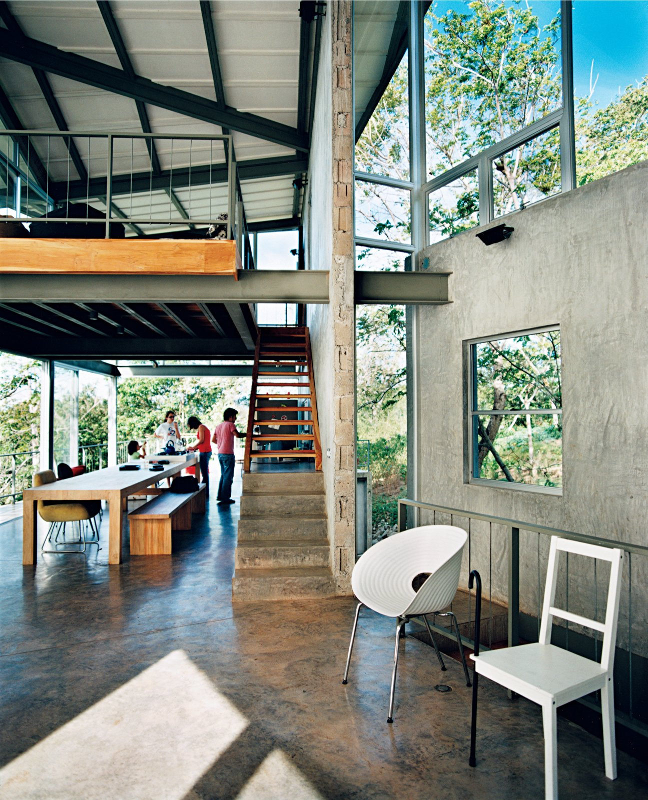 Exposed beams and a cantilevered loft soar over the high-traffic eating area, giving the family a sense of spaciousness. Tagged: Living Room, Concrete Floor, Chair, and Bench.  Photo 4 of 8 in Welcome to the Jungle