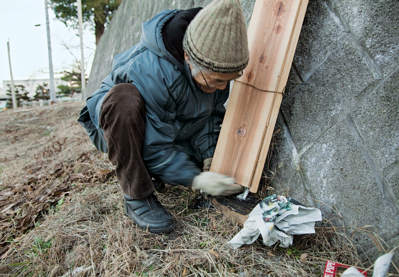 Fujimori, demonstrating the process of charring cedar boards, packs newspaper into the base of three planks that have been bound together.  Photo 13 of 23 in Terunobu Fujimori