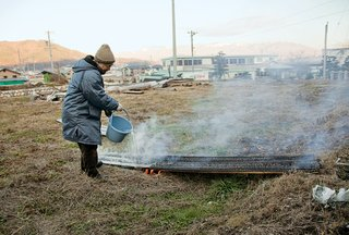 Terunobu Fujimori - Photo 18 of 23 - The craftsman pours water over the boards to halt the charring process.