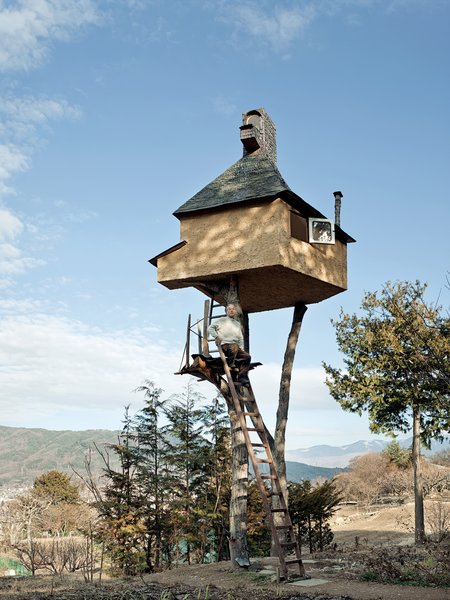 "Fujimori's retreat in Nagano, The Too-High Tea House, which is adorned with a roof of hand-rolled copper sheets, seems precariously perched atop a pair of tree trunks 20 feet in the sky. Why two? ""One leg is dangerous and three legs are too stable and boring."""