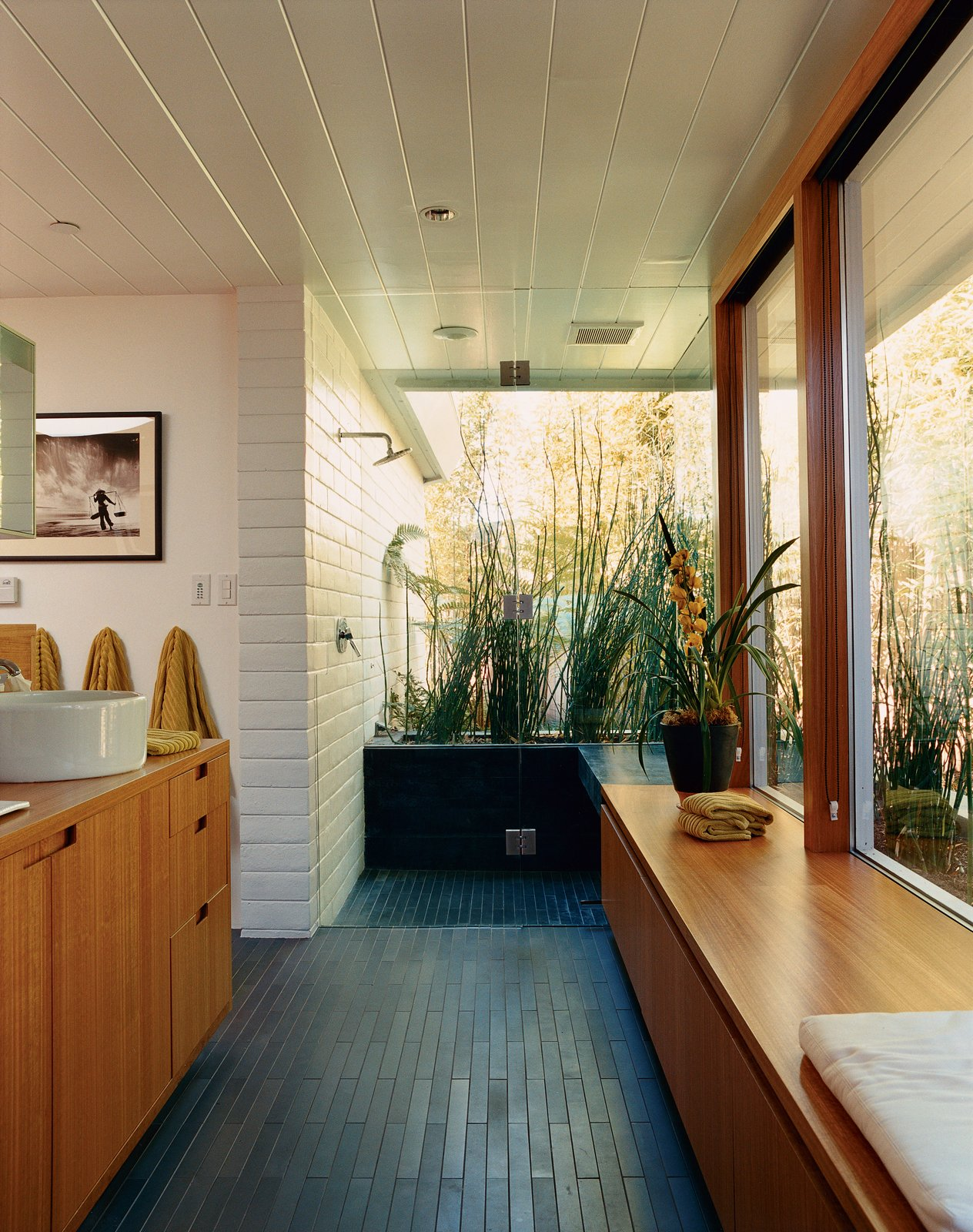 In the master bathroom, all boundaries between inside and outside and public and private are virtually eliminated. The dark tiles are by Ann Sacks. Baths by Lara Deam