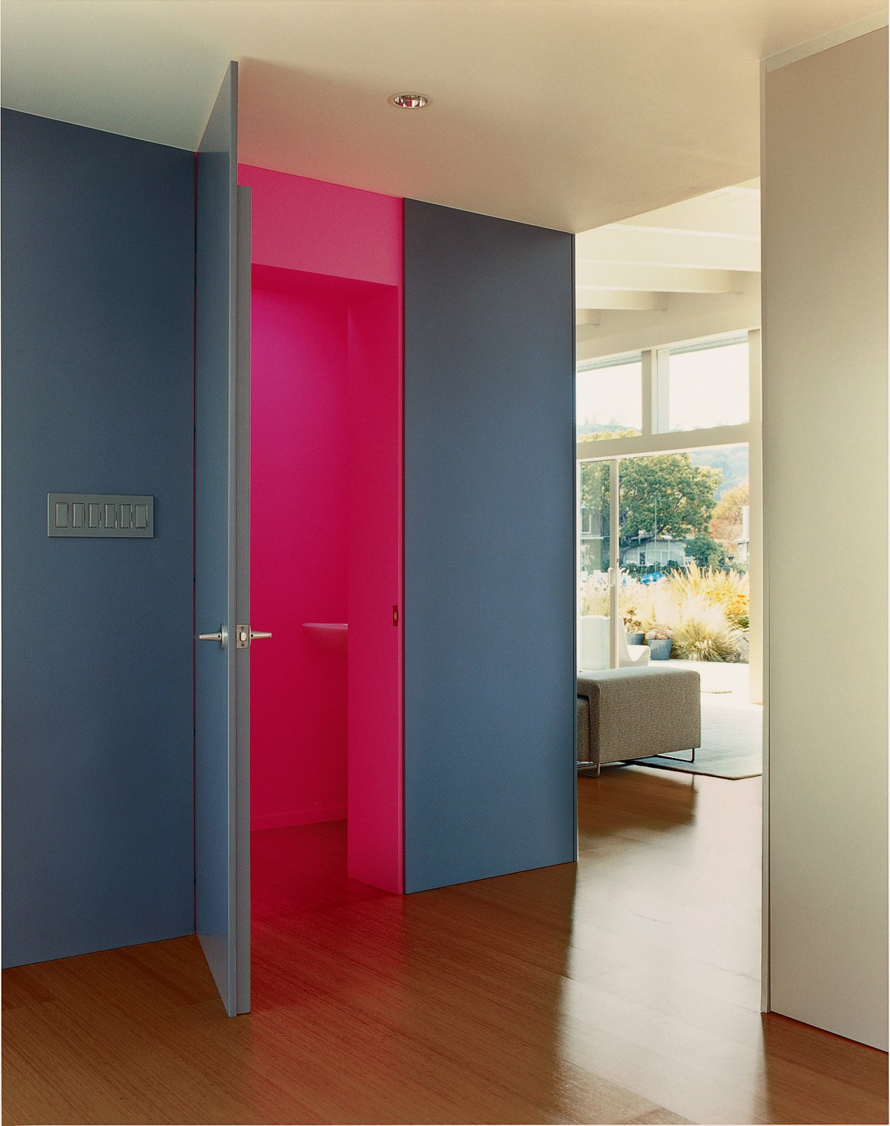 In the foyer, Deam left one surprise: The neon-pink guest bathroom is hidden behind heavy, dark-gray walls.  Composition by Lara Deam from The Bellwether of Belvedere