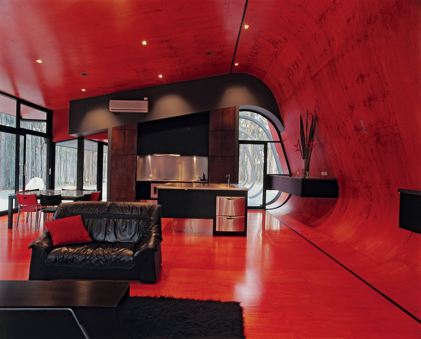 The glowing interior palette of bright pinks and reds is sharpened by jet-black steel frames, water tanks, and roofs, while black window frames and joinery bring out the red glow of the internal plywood lining. Tagged: Living Room, Sofa, and Rug Floor.  Best Photos from Black, Red, and Green All Over