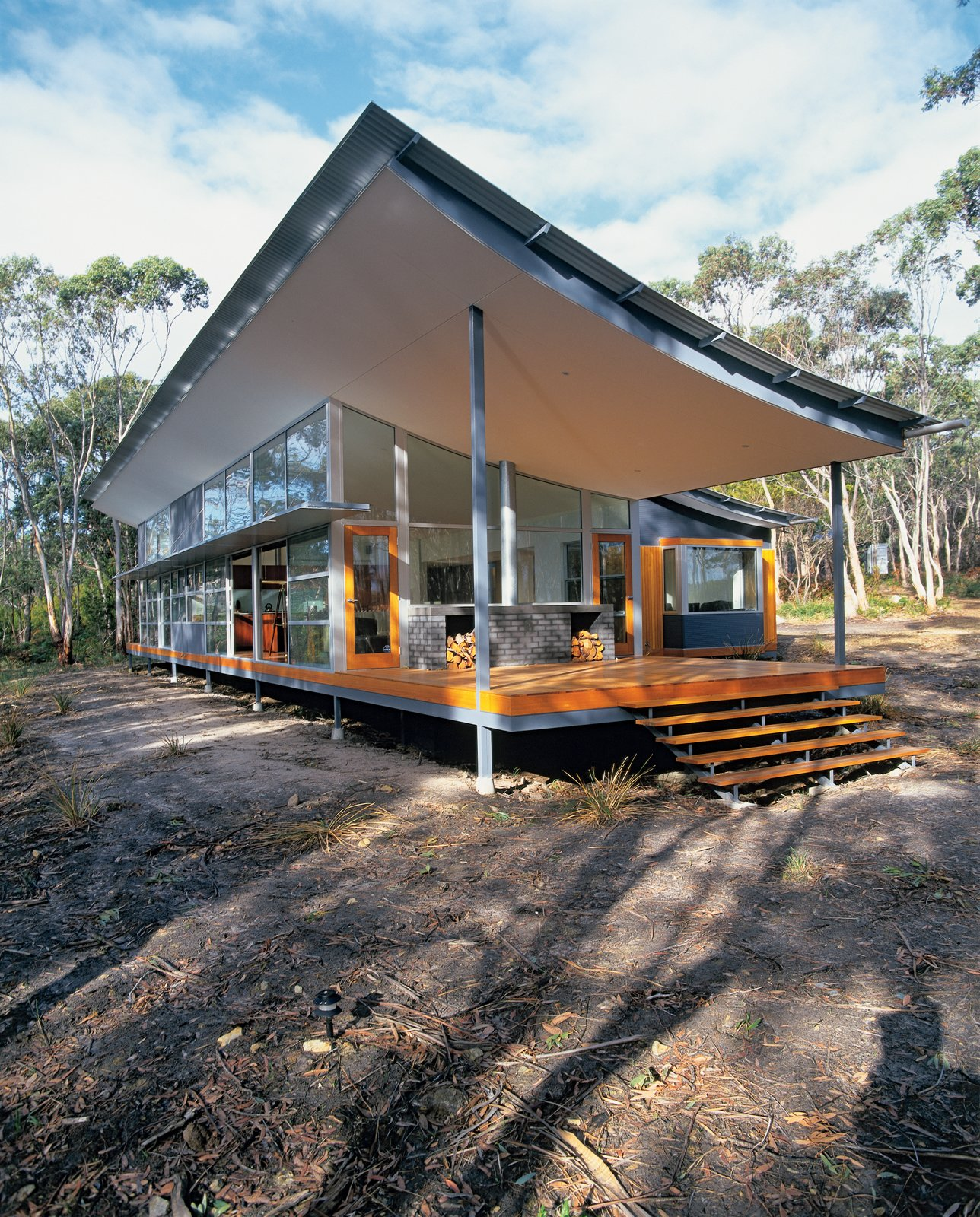 Solar panels mounted on a shipping container onsite (not pictured) heat this curvy house in Tasmania. The swooping roof cantilevered over the west-facing desk mitigates the intense afternoon sun.