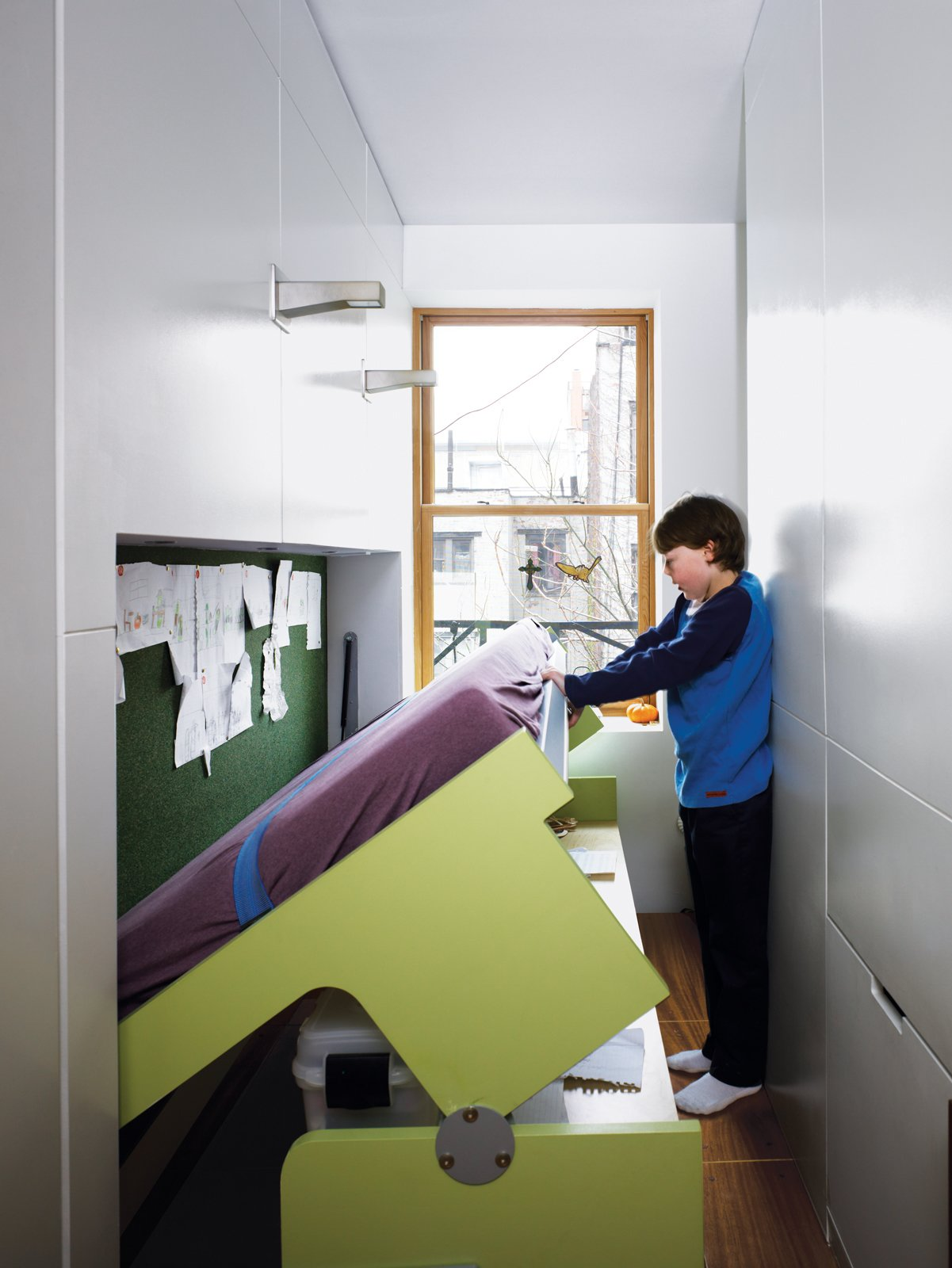 All it takes is gentle downward pressure to lower the desk to the floor, bringing the kid-size mattress into position for bedtime.  Photo 6 of 11 in These 10 Tiny Apartments in New York City Embrace Compact Living from Storage-Smart Renovation in New York City