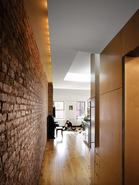 Although the apartment's only windows are on the far ends of the space, skylights keep things bright. Recessed lighting along the brick wall supplements the daylight.
