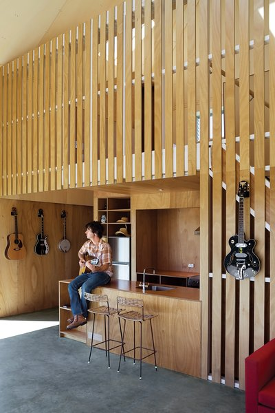 Music is central to Andrew McKenzie's living arrangements. With guitars hanging on his Gaboon plywood walls, he always has an instrument at hand.