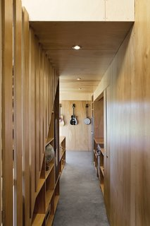 The corridor by the staircase leads to the kitchen and offers storage space.