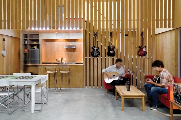 """Guitarist Andrew McKenzie built his first home squat in the middle of a commercial apple orchard. Resembling a floating barn on the exterior, the interior is all modern, including McKenzie's choice of """"honest"""" plywood walls over New Zealand's popularly-used GIB (a brand of plasterboard). A high ceiling - viewable as an asymmetrical apex from the outside - aids acoustics and makes the home feel larger than its modest 26x26 footprint. Read more about the McKenzie Residence here."""