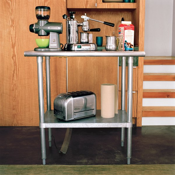 The kitchen island—–an equipment stand purchased from online restaurant supplier Serv-U—–is essential in providing much-needed counter space. The bottom shelf creates additional storage and the outlets mounted underneath allow it to become a coffee and toast center. Because it's stainless steel, the family can put a hot pan right on the surface without worrying about trivets—–which are hard to keep handy in such a small place.  Photo 8 of 9 in Built-In Style
