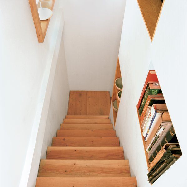 The stairway features built-in shelving that's accessible from both sides.