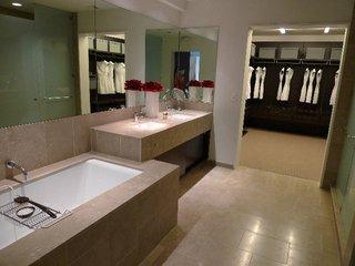 The bathrooms feature fossilized Brazilian limestone, Kohler fixtures, and Poliform closets.