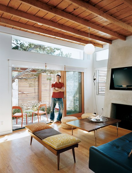 Architect, builder, and developer Jeremy Levine stands at the threshold of the front deck and the living room under his newly raised ceiling made of wood recycled from the original pitched roof.