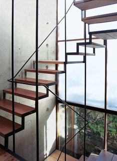 The wood-and-steel open staircase wends its way up three stories, supported by a concrete structural wall embedded with PVC tubes and bare lightbulbs.