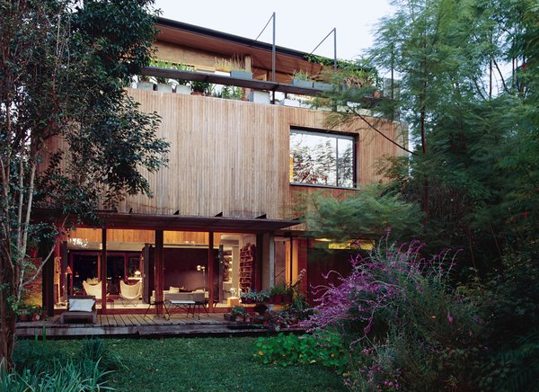 "Even the economy has regions, Alejandro Sticotti and Mercedes Hernaez discovered when Argentina's economy collapsed. This led them to build a house from local woods and materials, creating a house that is ""of Argentina""—and proud of it. Here, a ground-level patio and third-floor deck overlook a lush front garden; sitting out there is like ""being on vacation,"" says Hernaez."