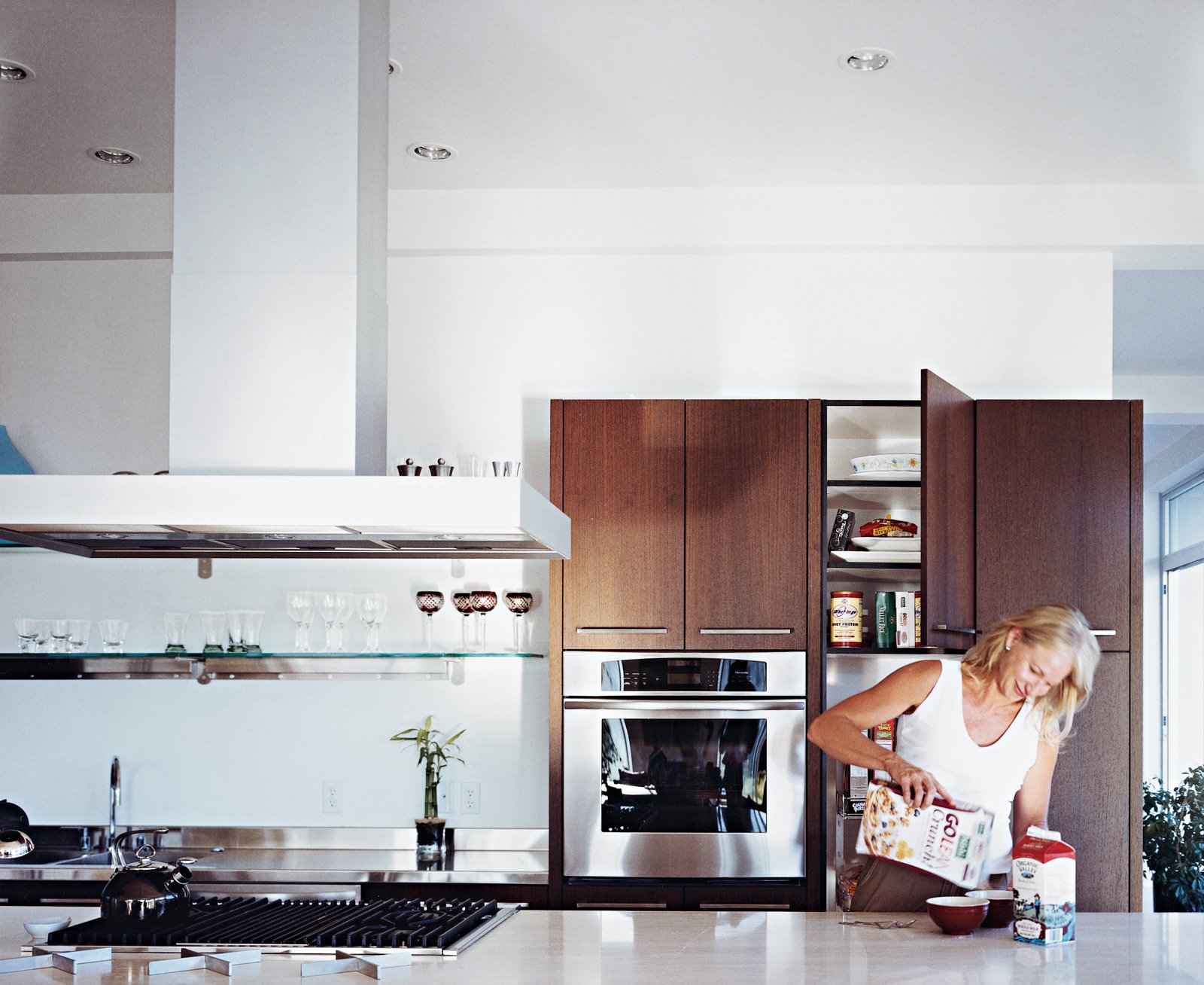 Jill prepares breakfast in the custom kitchen, which features a Roman travertine-topped work island. Tagged: Kitchen, Wood Cabinet, Range Hood, and Wall Oven.  Photo 6 of 9 in Modern Awakening