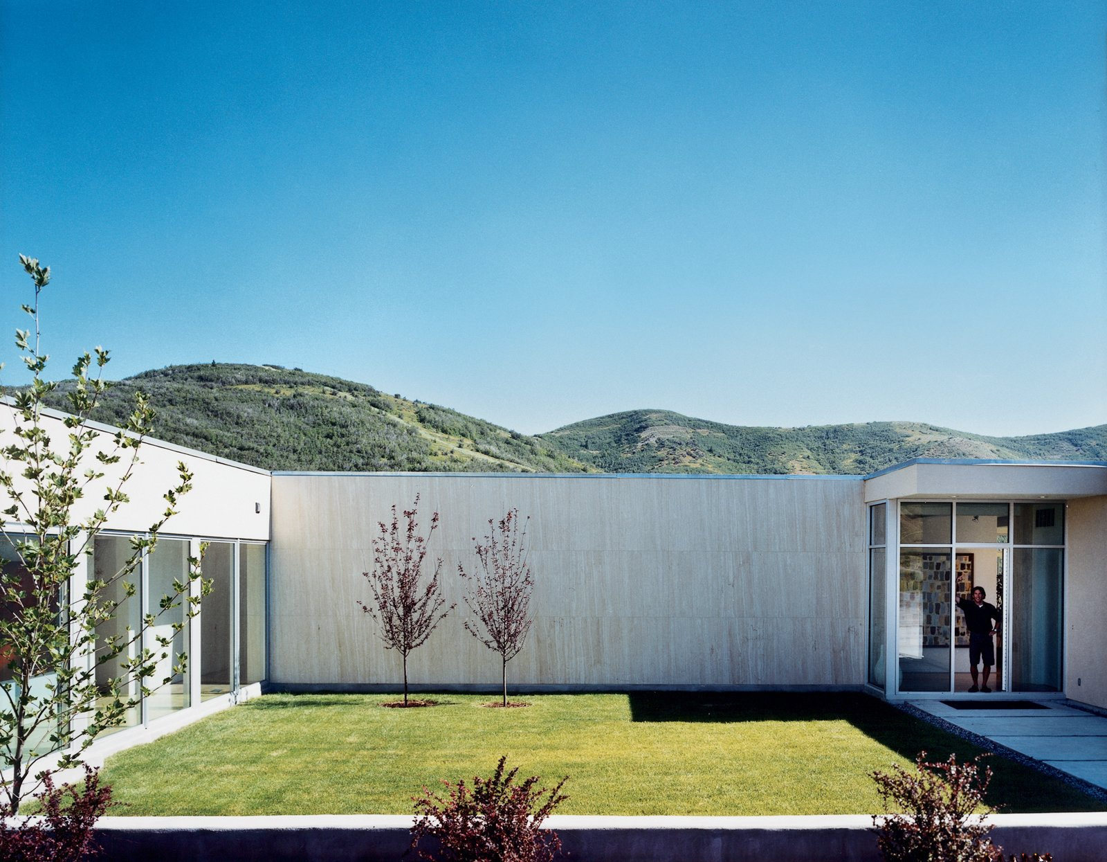 The landscaping appears to be based on the mullet principle: business in the front, as seen here (manicured grid lawn, with native vegetation sprouting in careful symmetry), party in the back (sunflowers and wild mountain grass growing in harmonious chaos). Tagged: Outdoor, Grass, and Back Yard.  Modern, Off-the-Grid Homes by Aileen Kwun from Modern Awakening