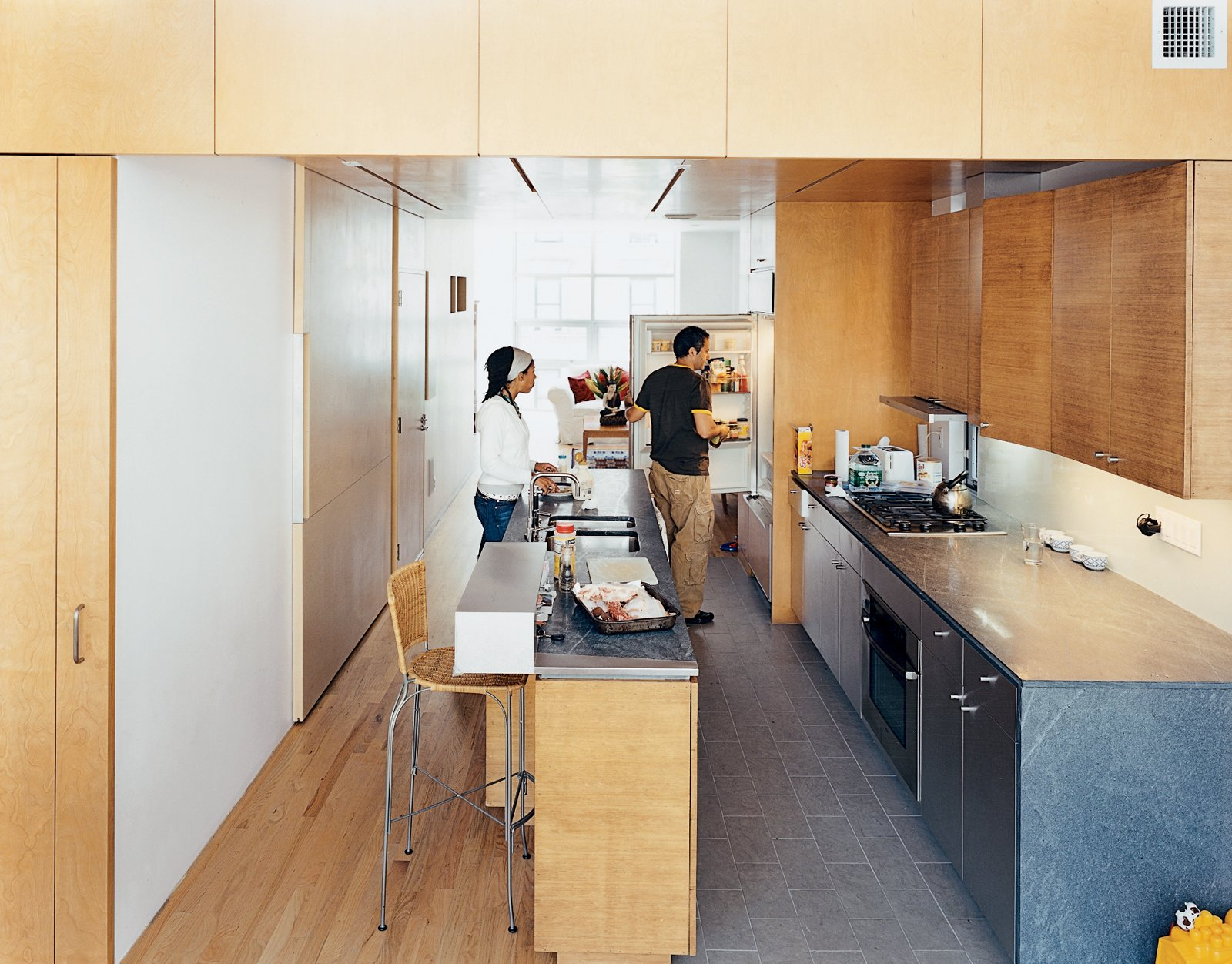 """In the kitchen, the architects contrasted the oak floor, bamboo cabinetry, and birch walls and ceiling with what architect Jonathan Knowles calls """"a family of grays"""": granite floor tiles, limestone countertops, and the steel stairway. The birch wall behind Yvette is actually the sliding door to the pantry closet."""