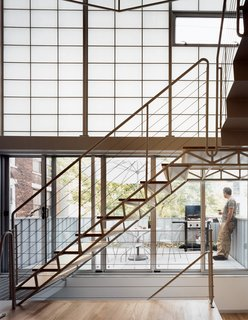 Seemingly a single, seamless unit, the stair is composed of two elements—treads and mezzanine—and held in place by two distinct strategies: The stairs are welded to, and cantilever out from, a series of steel tubes concealed in the walls; the mezzanine <br><br>is attached on one side to a steel beam, and hung at two other points from rods attached to the roof structure.