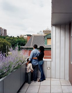"Yvette, Adrian, and their son Julian survey the view from the top-floor terrace. ""I've never been fond of modernism—I find it cold,"" Adrian admits. ""But having this house, I have <br><br>to say, it's growing on me."""