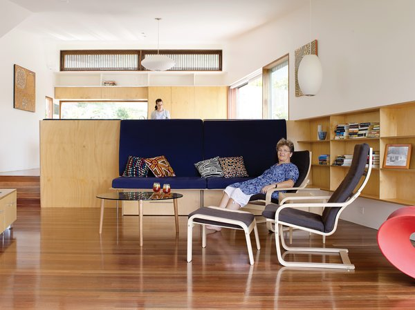 Pedigree Charted - Photo 3 of 10 - Hannah Ferguson relaxes in her living room. Her daughter Joanna prepares dinner in the open kitchen, behind and above the plywood banquette designed by the architects.