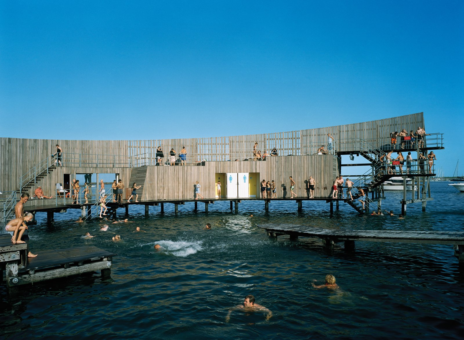 The sea bath's shape creates great acoustics, which local musicians frequently take advantage of by performing impromptu concerts in the middle of the structure. As the structure curves around, two pathways are formed: The outer path ascends into a diving platform, and the inner path remains level, for wheelchair accessibility. Photo by Åke E:son Lindman.  Photo 2 of 2 in Dunkin' Danish