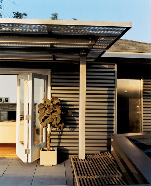 Day skinned the house in corrugated-aluminum siding, a tough industrial palette he picked up while designing airports. The corrugated stainless steel canopy was fabricated by Day's former SCI-Arc classmates.