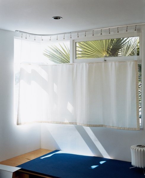 The lower-level guest room, which makes inventive use of a hospital curtain.
