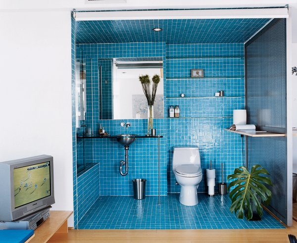 A roll-down shade encloses a guest bath on the lower level. The bath tile is two-by-two Daltile mosaic. The sink is from Kroin.