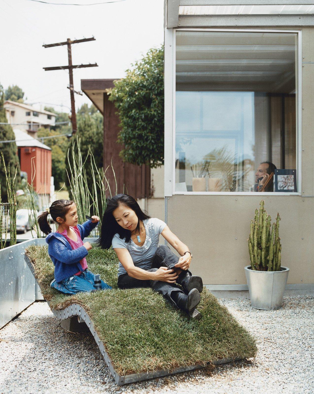 Téa gets mom ready for her close-up on the curvy nature-meets-industry chaise lounge of the architects' own design. The landscaping in front and out back is characterized by sturdy, resilient, and drought-resistant plants like bamboo and cacti, cultivated in galvanized steel planters.  Photo 5 of 9 in How This Couple Broke The Rules in a LA Suburb
