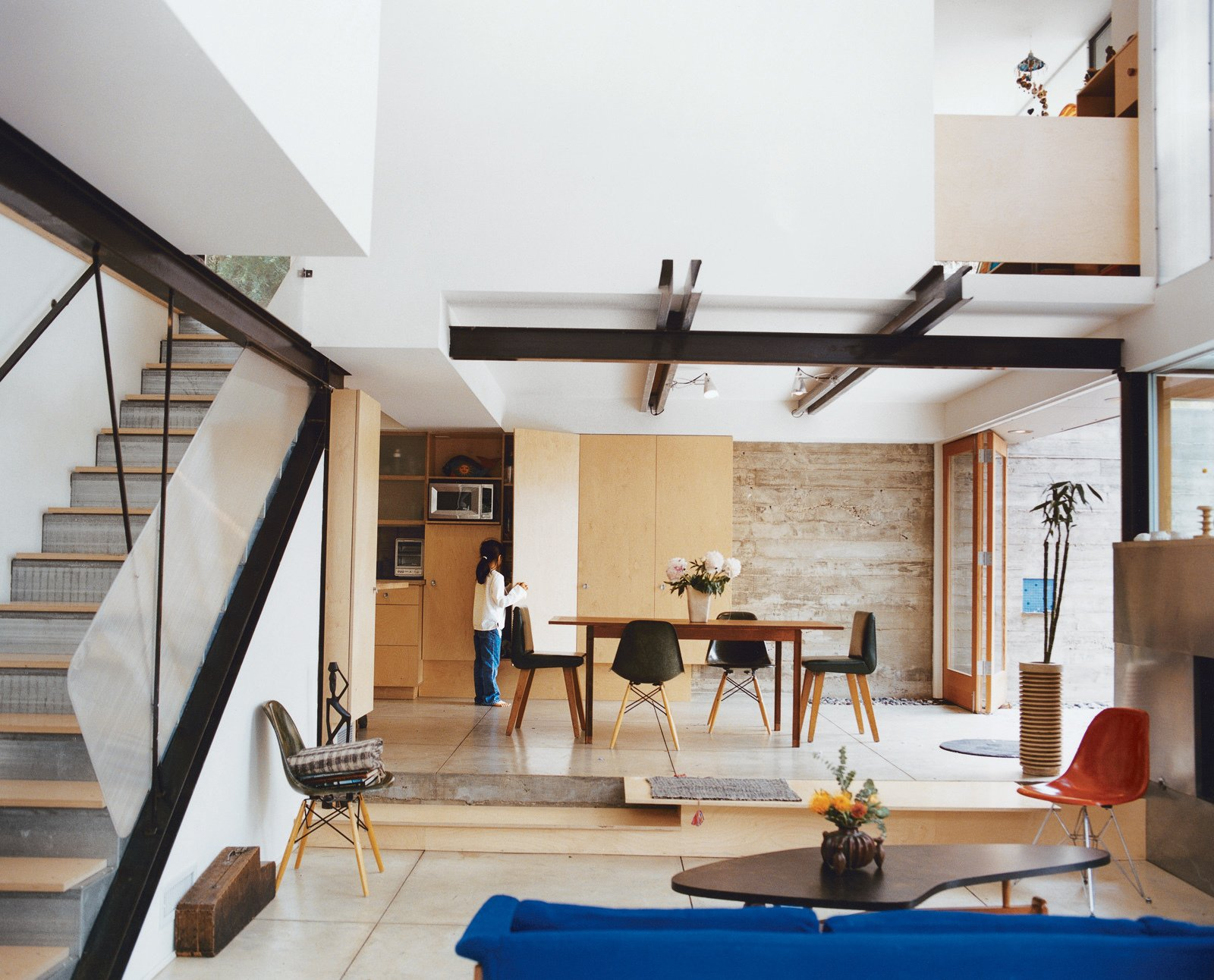 """The steel framing used for the house was left partially exposed. Other pragmatic touches with longevity and economy in mind are evident throughout, such as the screwed-down birch plywood stair treads that can simply be flipped over when worn out. Most seating below by Charles and Ray Eames. The coffee table by Paul Laszlo is, says Fung, """"probably the nicest thing we own."""" Tagged: Dining Room, Chair, and Table.  Photo 9 of 20 in 20 Modern Living Rooms from How This Couple Broke The Rules in a LA Suburb"""
