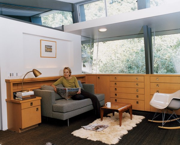 "Buckner takes time out for the newspaper and a cup of tea in a lounge off of the couple's bedroom. The bedroom, which sits within the cantilevered section of the house, was at one time a covered deck. The storage units are from a later renovation, but Buckner, who has expert knowledge of all of the original MHA homes, surmises that ""something very similar"" would have been in its place."