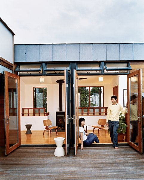 Jinhee Park and John Hong, in a doorway that opens to the building's shared roof deck. Behind them is the upstairs lounge of their neighbors, adorned with Eames chairs, Kartell stools, and a woodstove from Rais Wittus.
