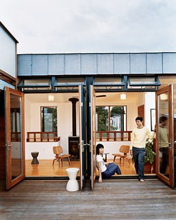 Beantown Dream - Photo 2 of 11 - Jinhee Park and John Hong, in a doorway that opens to the building's shared roof deck. Behind them is the upstairs lounge of their neighbors, adorned with Eames chairs, Kartell stools, and a woodstove from Rais Wittus.