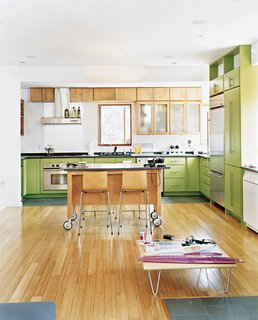 Knowing that Andy's multi-tasking begets clutter, John provided him with plenty of cabinets. By making very particular requests of The Home Depot—asking for irregular-sized doors and painting them electric green—John defied the generic look of big-box cabinetry.