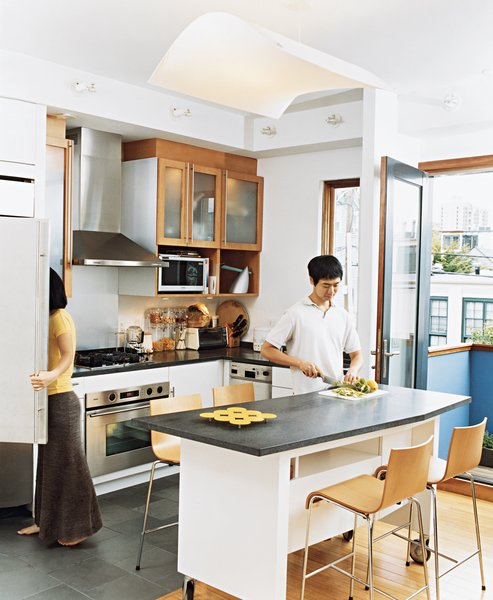 Avid cooks, Jinhee and John spend part of every day around their custom-built kitchen<br>island, surrounded by Compasso d'Oro barstools. An edamame plant on their patio occasionally provides leaves for Korean dishes.