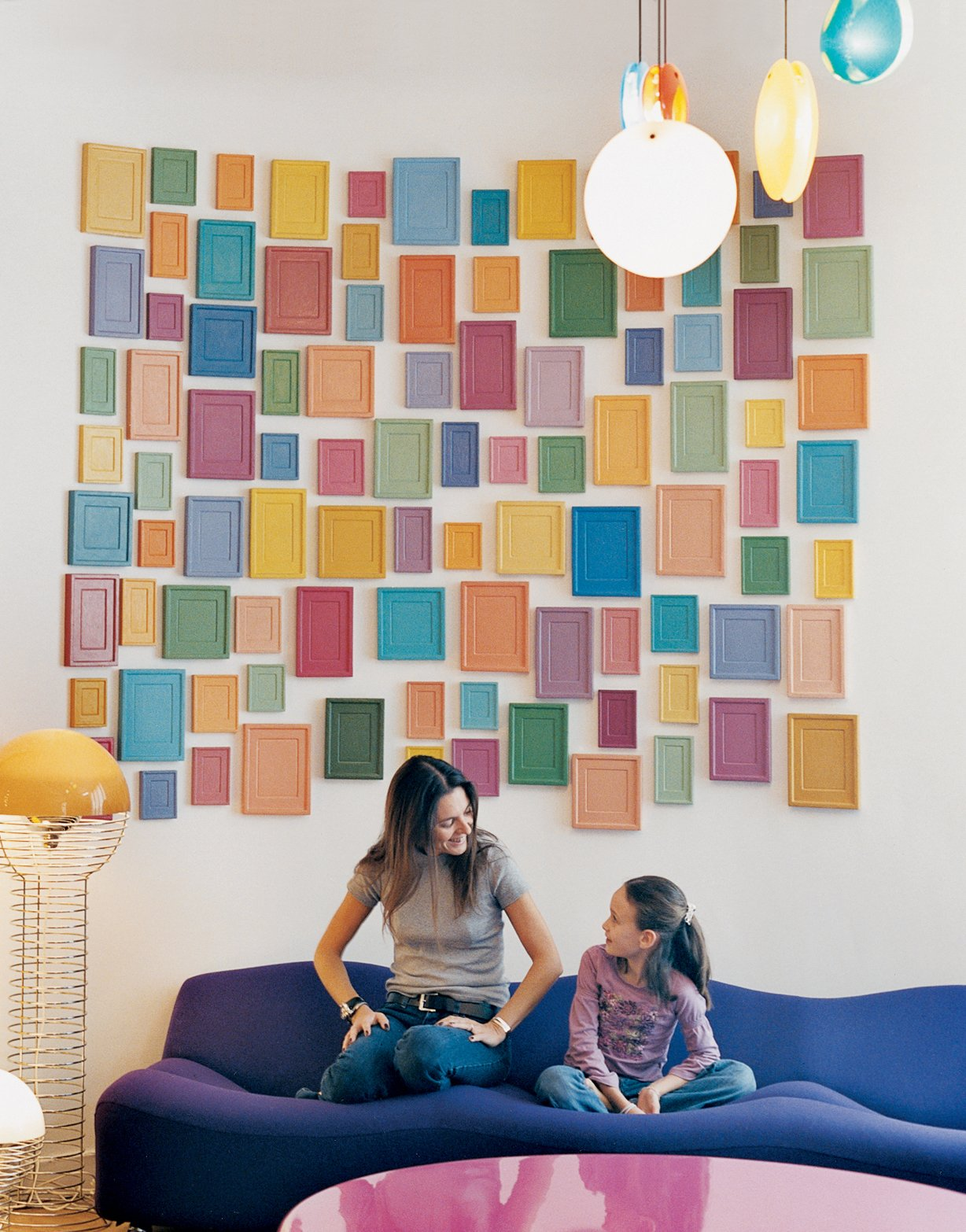 Clémence and daughter Clara, nine, relax on a purple Pierre Paulin 261 sofa below an installation by artist Alan McCollum. A small family of Verner Panton 1969 Wire lamps, featured in the inaugural Kreo exhibition, live to the left. Tagged: Living Room, Sofa, and Pendant Lighting.  Photo 6 of 15 in How to Design with Pink from Like a Kid in a Candy Store