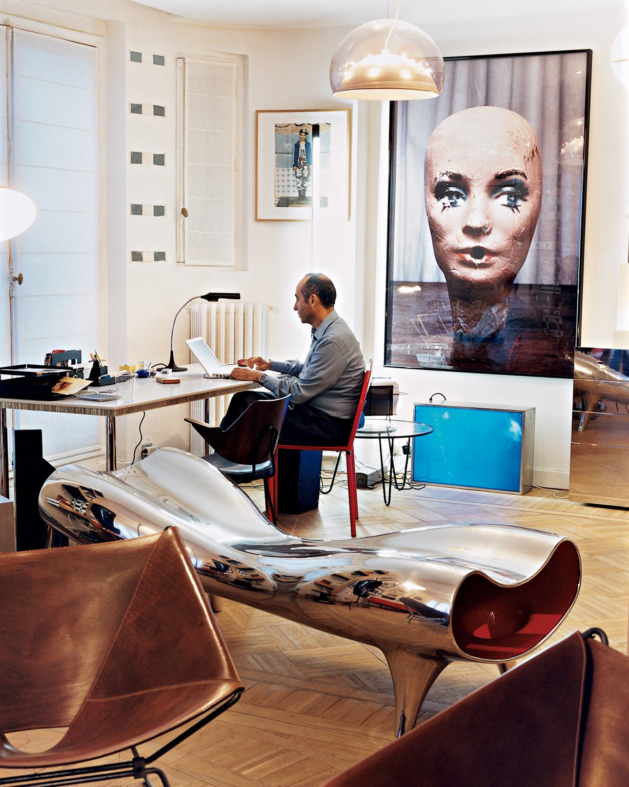 Krzentowski, who works from home for three hours a day, at his desk. A Marc Newson Orgone stretch lounge occupies the foreground, while a large Paul McCarthy photograph looms behind.