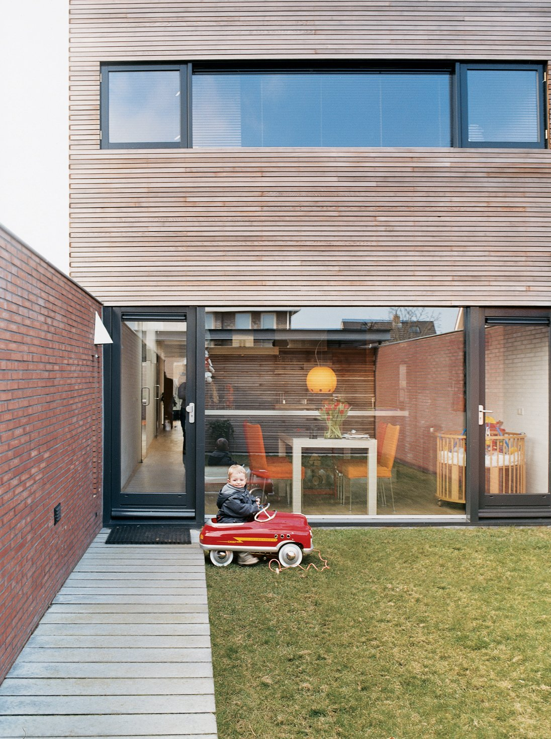Because the Collette residence, although by no means small by Dutch standards, is a compact 2,050 square feet, the inside/outside relationship is important. Glass walls front and back bring the outdoors in. Two-year-old Jort takes full advantage of the great outdoors. Tagged: Outdoor, Back Yard, Small Patio, Porch, Deck, Wood Patio, Porch, Deck, and Grass.  Photo 1 of 7 in Furniture Fascination
