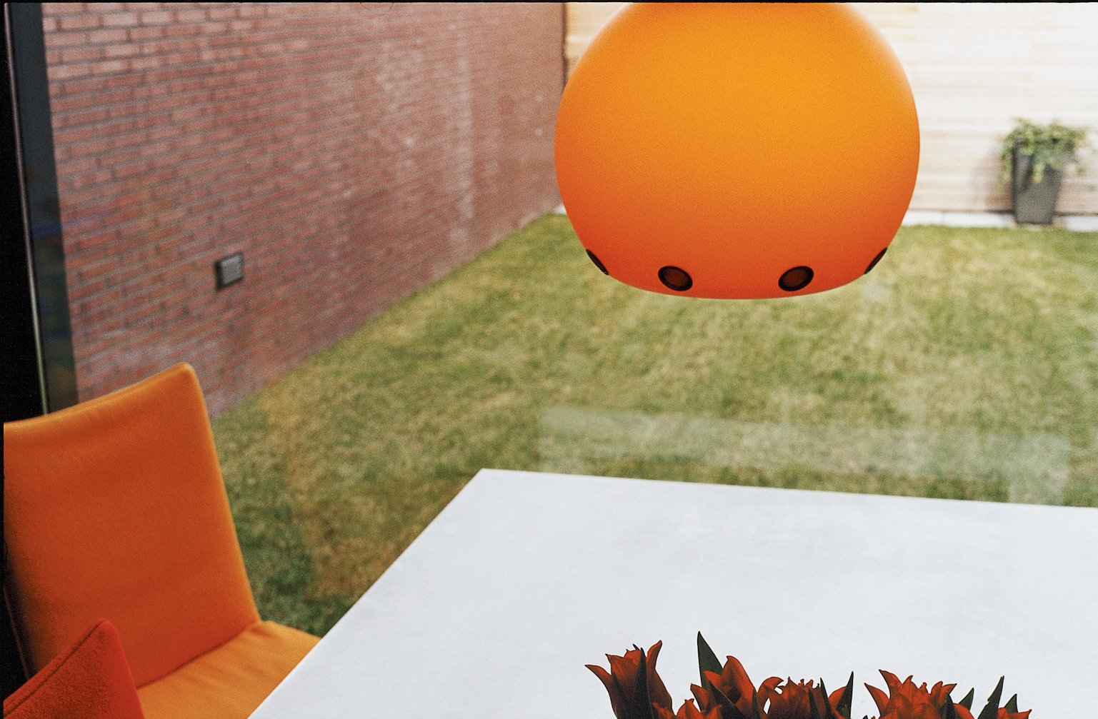 "The pumpkin-orange Dordoni Halloween lamp is both UFO- and sun-like—a slightly humorous and cheering sight on a gray day in Holland. It was chosen, says Dedy, ""simply because it says 'welcome home.'"" Tagged: Dining Room and Pendant Lighting.  Photo 5 of 7 in Furniture Fascination"