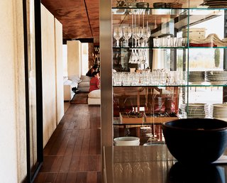 The ever-important Italian kitchen pours out through glass walls into the living room and onto the porch. A group of benches allows guests to hang out, drink wine, and pester the chef, while stainless-steel basins on rollers underneath give hungry kids easy access to snacks. Stainless-steel-and-glass shelving by the architects provides open storage for plates and glassware.