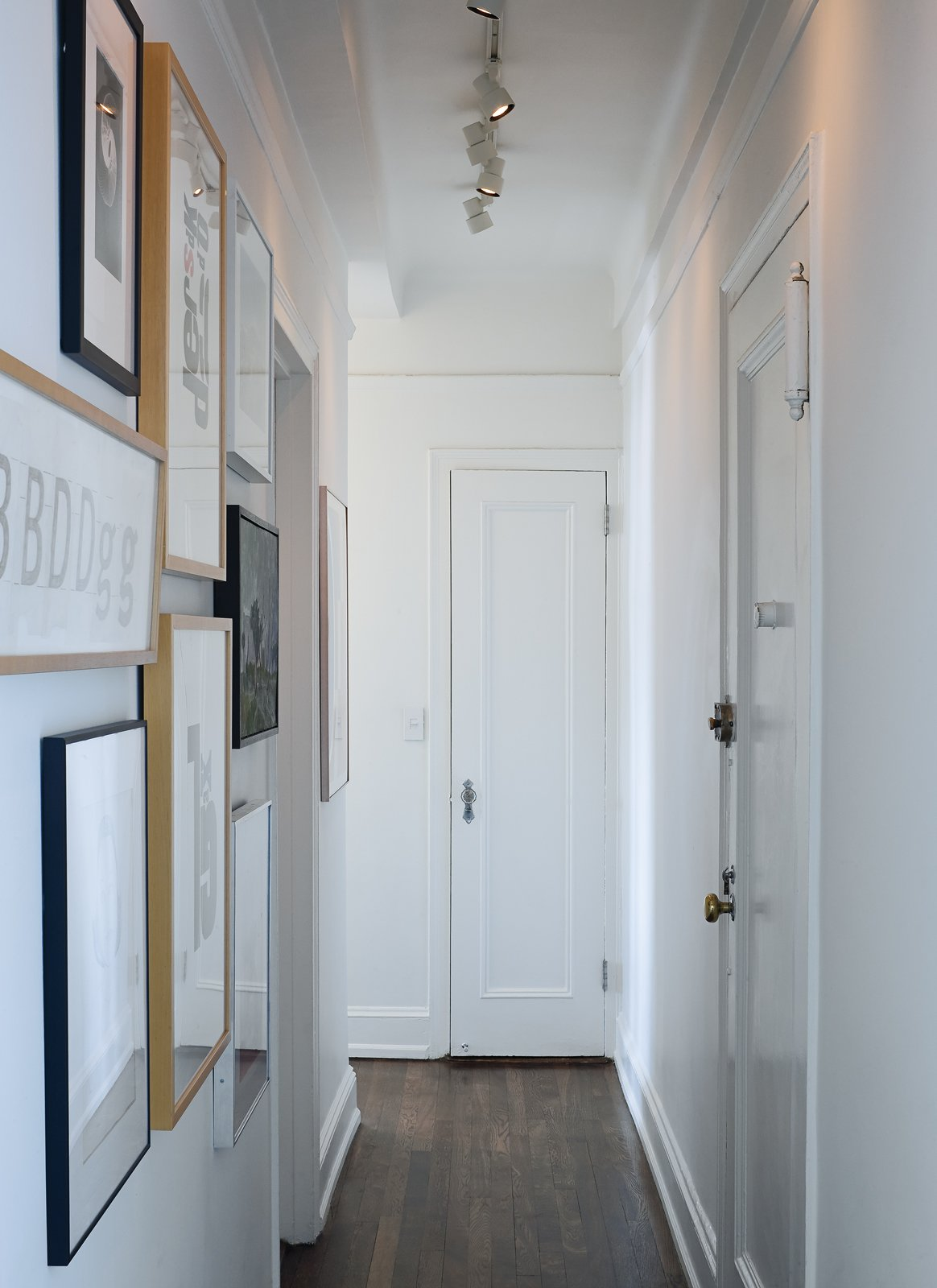 A narrow hallway, typical of prewar apartments, doubles as an art gallery lined with woodcut type studies by graphic artist Jack Stauffacher, type sketches by Erik Spiekermann, and photography by Catherine Opie and Catherine Ledner.  Photo 7 of 13 in Creative Renovation in Brooklyn