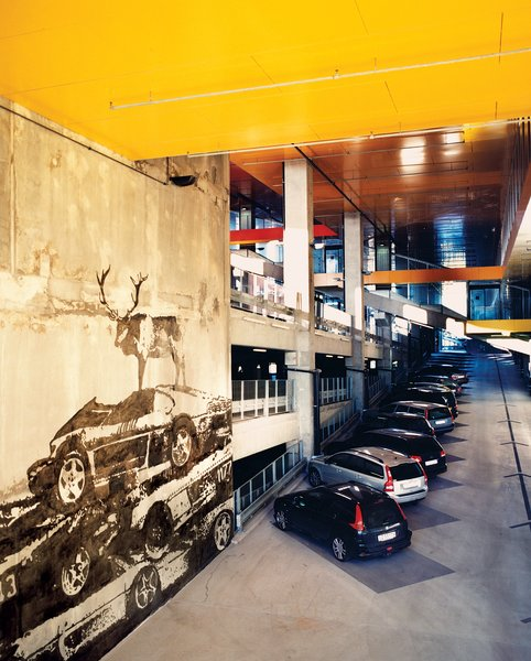 "Not content to just build a regular parking lot behind the Himalayan facade, Ingels created a high-ceilinged, five-story, concrete-and-steel ""car cathedral—to celebrate car culture."" Throughout, the French artist Victor Ash varnished the concrete walls with gray-on-gray murals of wild animals—a wolf, a moose—standing atop piles of wrecked automobiles."