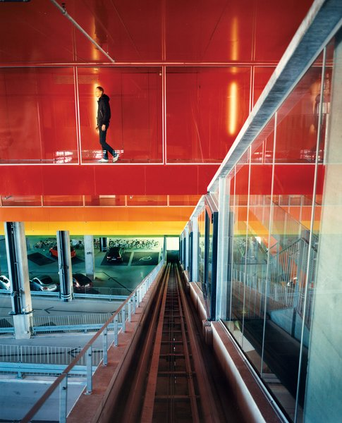 "The halls connecting the garage to the residences are covered in brightly painted aluminum treatment associated with cars, not buildings. The colors move, symbolically, from earth to sky: green, yellow, orange, dark orange, hot pink, purple, bright blue. ""Buildings are never brightly colored,"" says Ingels, explaining the thinking behind this stepladder rainbow, ""but cars often are."""