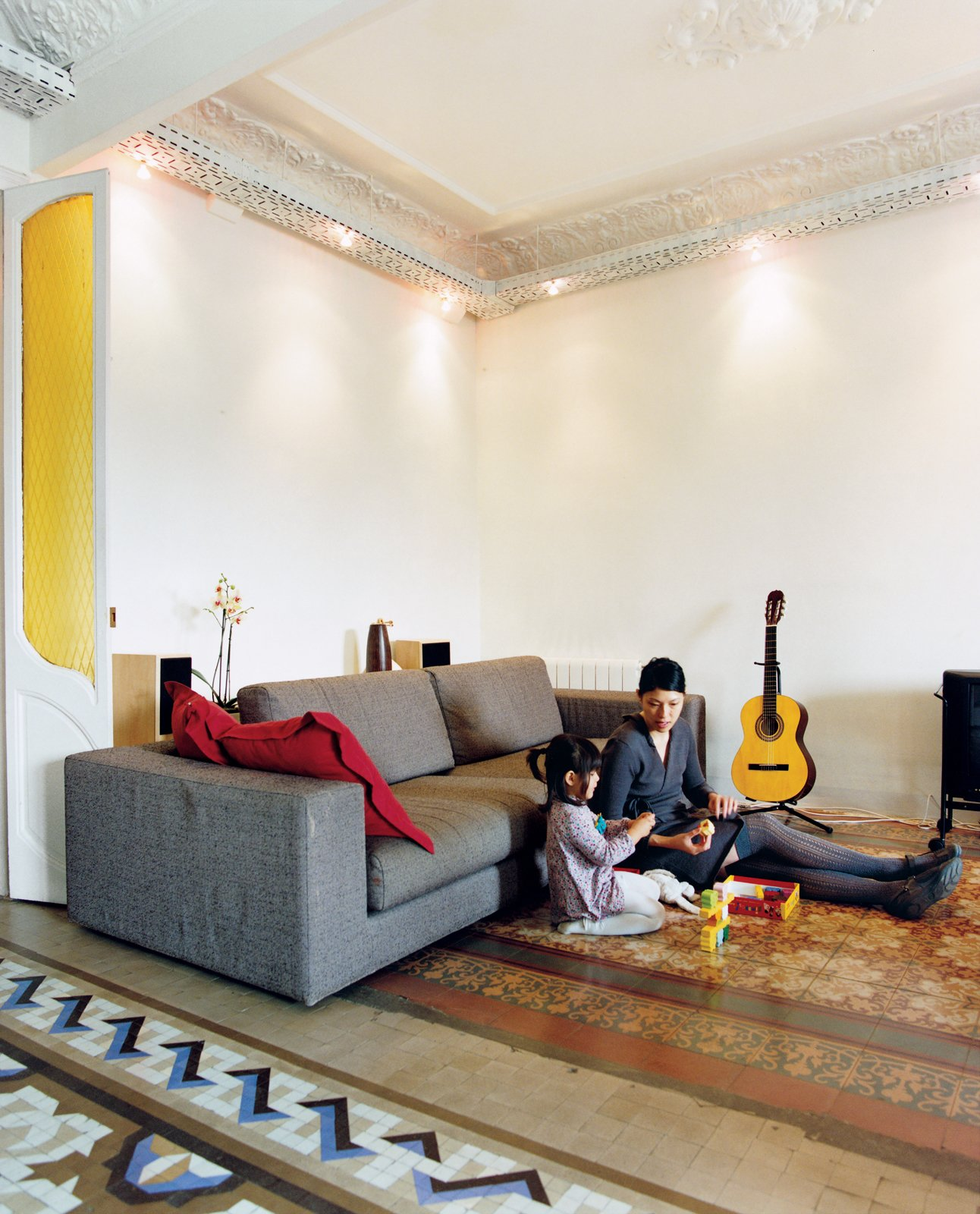 """""""We really fell for the building and these fabulous original features—–the elaborate decorative plasterwork ceiling and the tiled floors. Plus we have a big expansive view at the back, which is quite precious in the city—–we overlook a soccer pitch built on former railway tracks."""" Tagged: Living Room and Sofa.  Photo 2 of 6 in Renovating Old and New in Barcelona"""