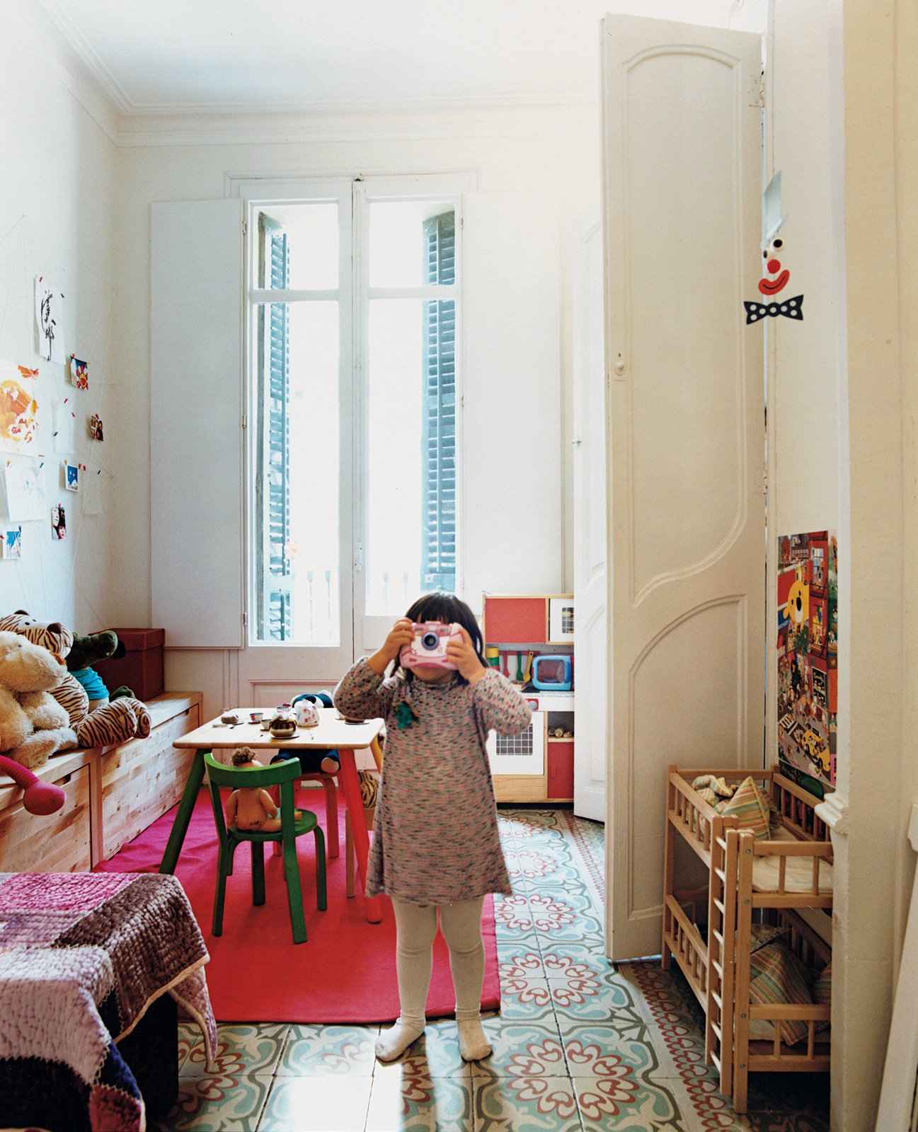 """It's typical for Barcelona buildings from this period that the bedrooms are divided with decorative plaster columns and a cornice to create a curtained-off alcove for the bed, separating it from the more public part of the rest of the room. We opened up our bedroom, but we conserved that feature in Hanna's room, and now every morning she wants to play dress-up."" Tagged: Kids Room and Bedroom.  Photo 4 of 6 in Renovating Old and New in Barcelona"